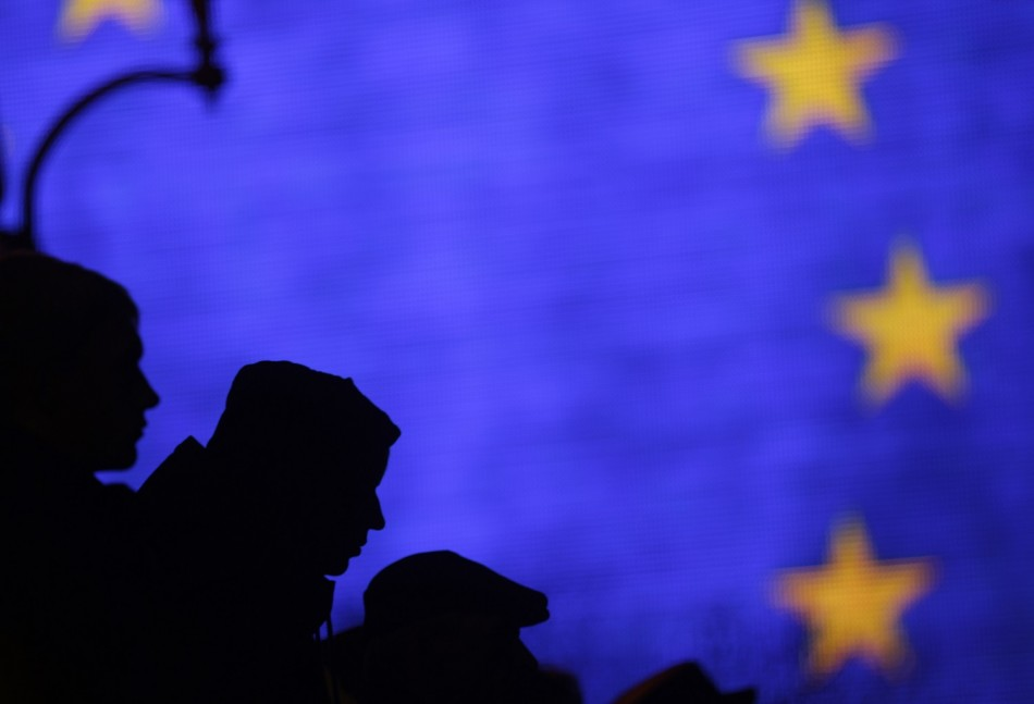Protesters are silhouetted against a giant screen displaying the European Union flag during a demonstration at Independence Square