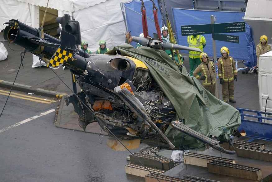 Emergency services remove the remains of the police helicopter which crashed in to the Clutha pub in Glasgow PIC: Reuters