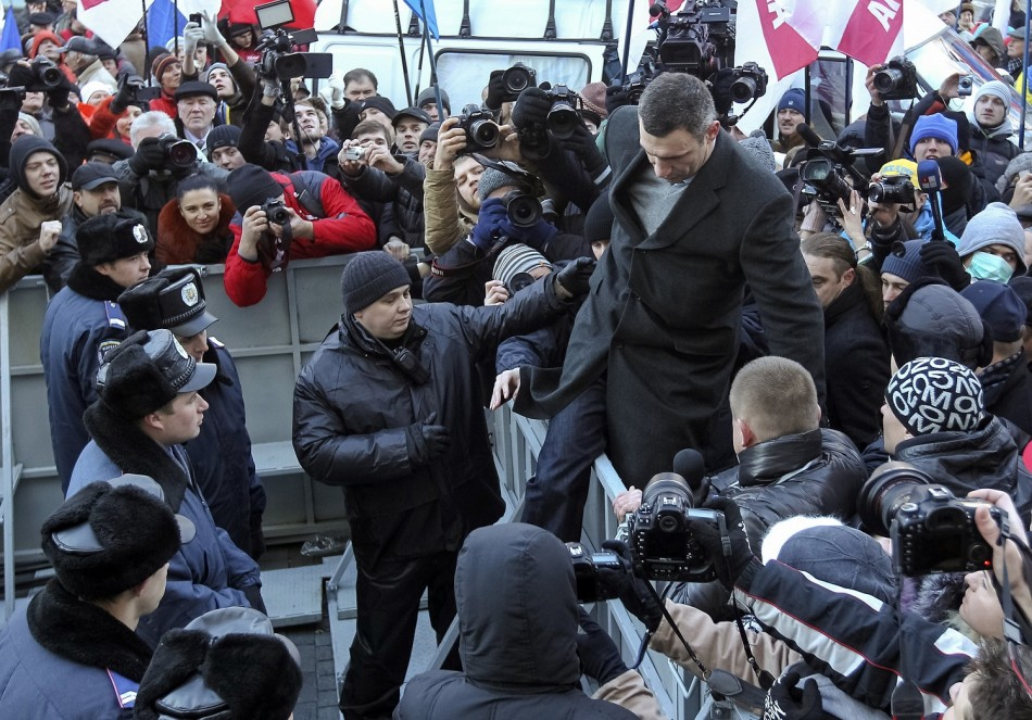 Heavyweight boxing champion and UDAR (Punch) party leader Vitaly Klitschko (top R) climbs over a police fence during a rally in support of EU integration in front of the Ukrainian cabinet of ministers building in Kiev
