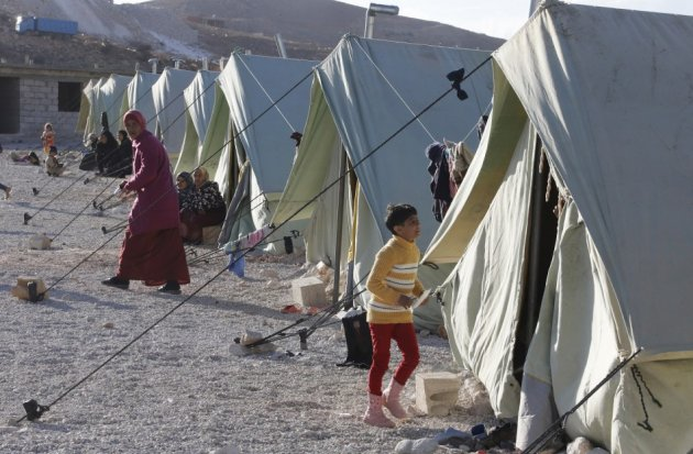 Syrian refugees are seen outside their tents set up by the U.N. at the Lebanese border town of Arsal, in the eastern Bekaa Valley
