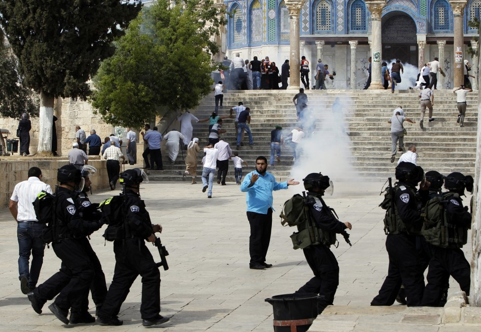Muslim worshippers run as tear gas fired by Israeli policemen rises during clashes