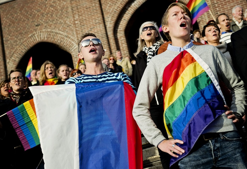 People sing the Russian national anthem while raising rainbow flags and a Russian flag (C) in solidarity with the lesbian, gay, bisexual and transgender (LGBT) community of Russia