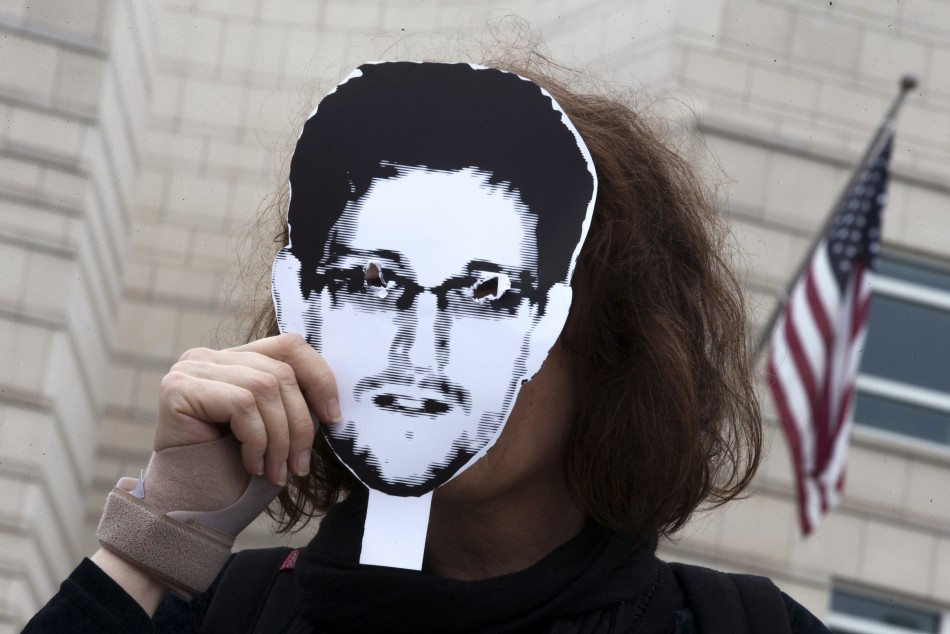 Woman holds a portrait of former U.S. spy agency contractor Snowden in front of her face as she stands in front of the U.S. embassy during a protest in Berlin in this file photo