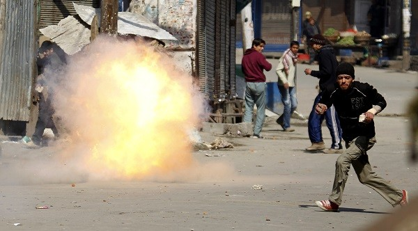 A Kashmir protester flees as a tear gas shell fired by Indian troops explodes nearly during a 2010 demonstration [].