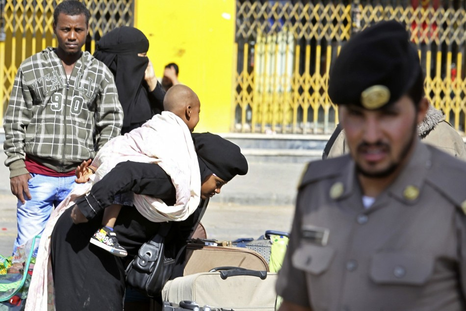 An Ethiopian worker carries her baby as she waits with her countrymen to be repatriated in Manfouha, southern Riyadh