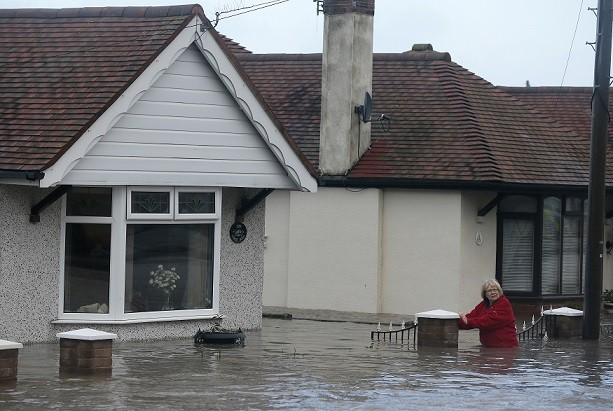 A woman walks through flood water in a street in Rhyl, north Wales (Reuters)