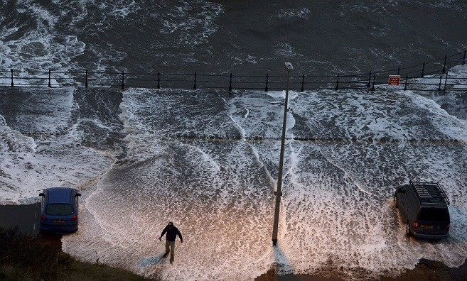 A man stands in water washed onto the promenade of the north bay in Scarborough (Reuters)