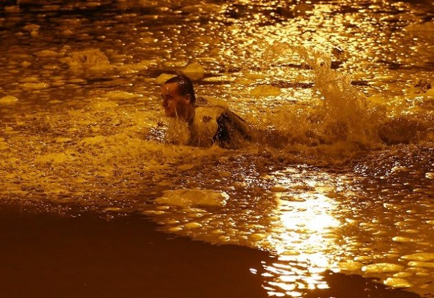 A man falls in flood water during the storm surge in Great Yarmouth (Reuters)