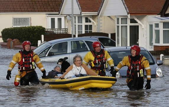 Emergency rescue service workers evacuate residents in an inflatable boat in flood water in a residential street in Rhyl (Reuters)