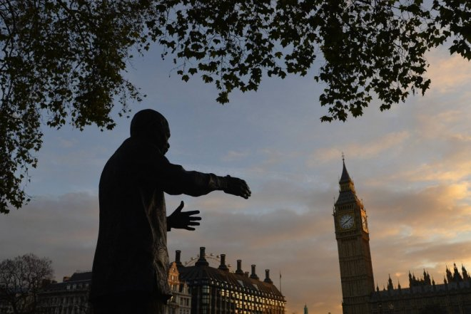 A statue of former South African President Nelson Mandela is seen with the Big Ben clock and the Houses of Parliament in the background at dawn in London December 6, 2013.