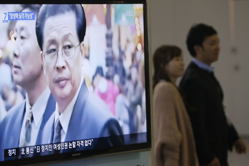 A couple walks past a television showing a report on Jang Song Thaek, North Korean leaders' uncle, at a railway station in Seoul