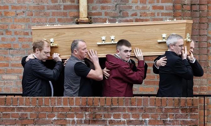 Liam O'Prey, (in burgandy jacket) helps carry the coffin of father Mark O'Prey at East Kilbride PIC: Reuters