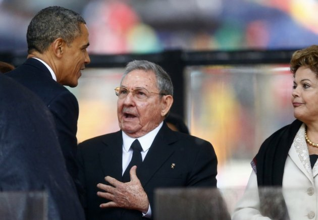 U.S. President Barack Obama (L) greets Cuban President Raul Castro (C) before giving his speech