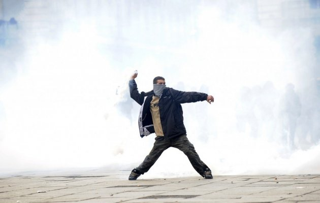 A protester throws a tear gas canister during a protest in downtown Turin