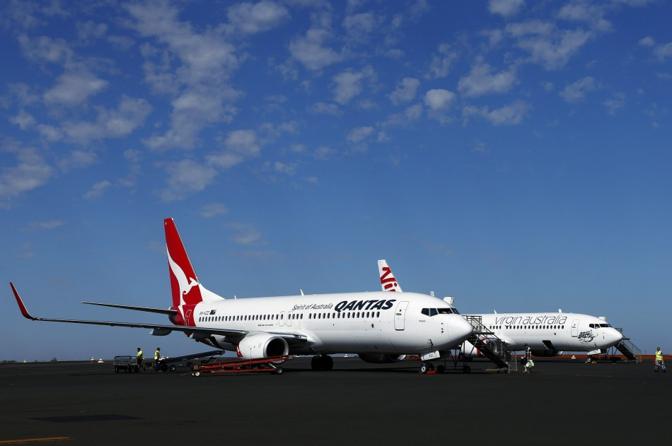 A Qantas Airlines Boeing 737 plane sits next to a Virgin Australia Boeing 737 plane at the Port Hedland airport in the Pilbara region of western Australia December 3, 2013. Ratings agency Standard