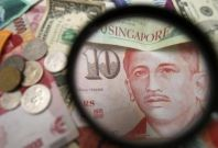 Singapore currency notes are seen through a magnifying glass among other currencies in this photo illustration taken in Singapore April 12, 2013.