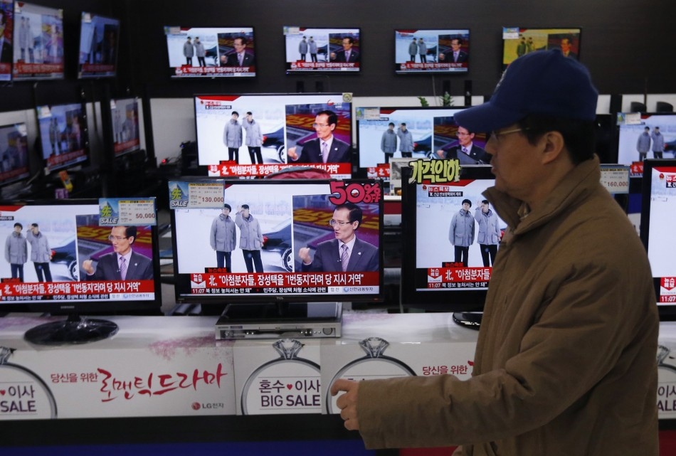 A man walks past televisions showing reports on the execution of Jang Song Thaek at an electronic store in Seoul December 13, 2013. (Reuters)