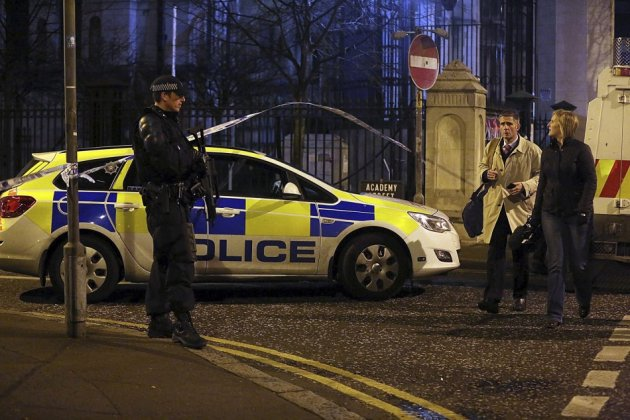 An armed policeman speaks to a member of the public near the scene of an explosion in Belfast's Cathedral Quarter