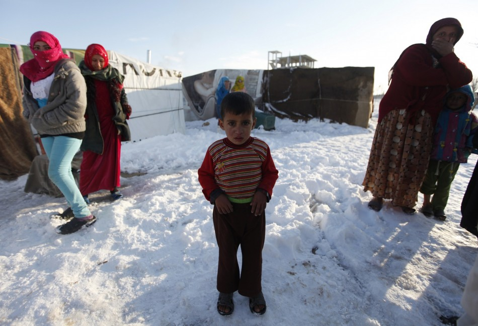 A child refugee from the northern province of Raqqa in Syria, reacts from the cold weather in a Syrian refugee camp beside the Lebanese border town of Arsal, in eastern Bekaa Valley