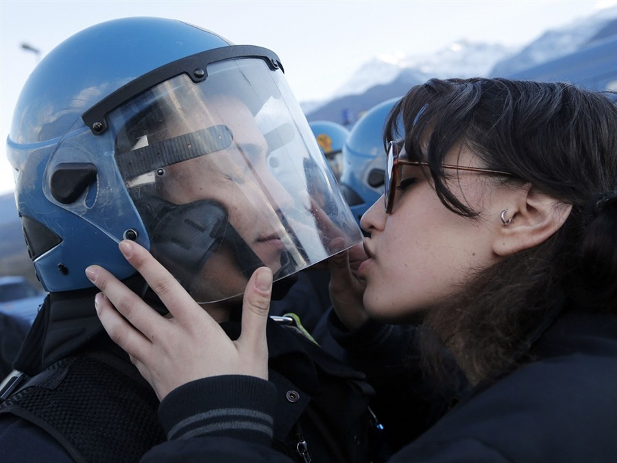Protester kisses riot officer's visor