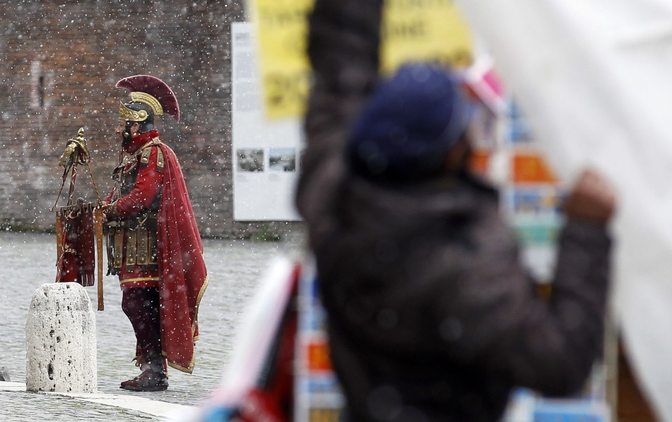 A man dressed as a centurion outside Rome's Colosseum in the December snow.