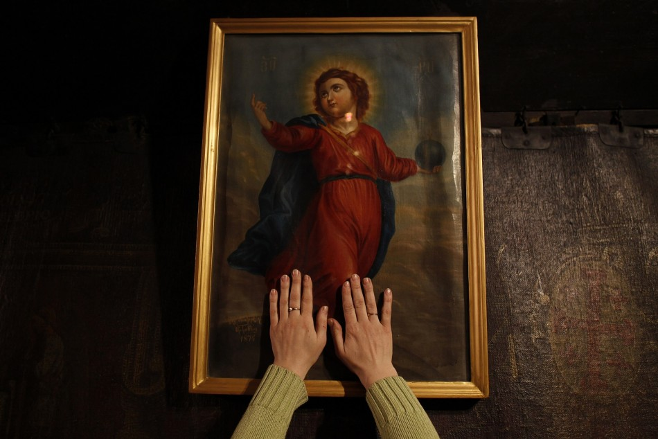 A worshipper places her hands on a painting of Jesus in the Grotto, where Christians believe Virgin Mary gave birth to Jesus, during her visit to the Church of the Nativity in the West Bank town of Bethlehem