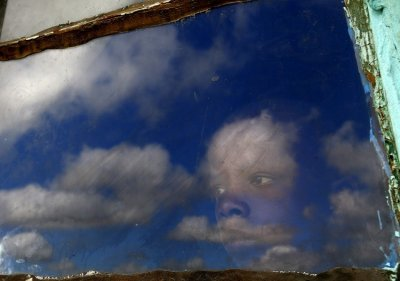 A local boy, Anda, looks out from his huts window at the burial ground of late former South African President Nelson Mandela ahead of his funeral in Qunu, December 15, 2013. Reuters picture
