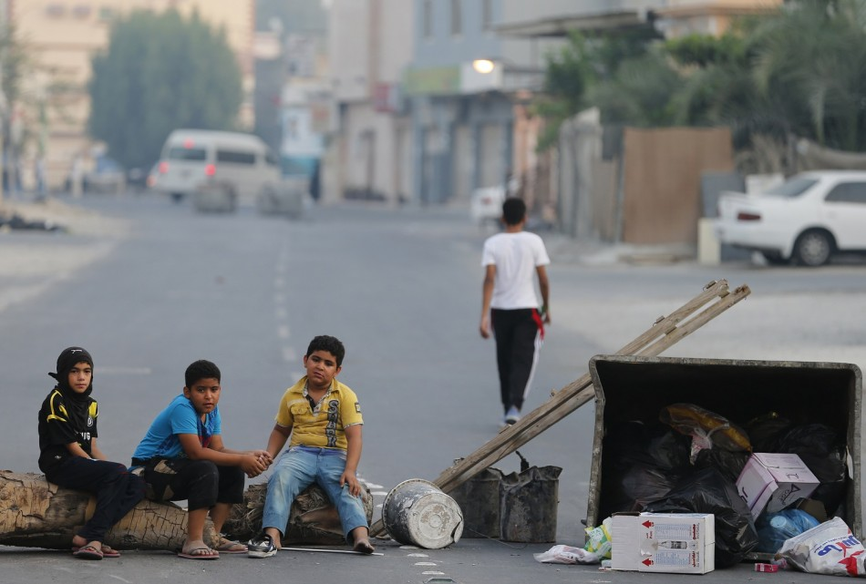 Children sit on a roadblock set up by protesters to prevent riot police from entering the village of Shakhoora, west of Manama,