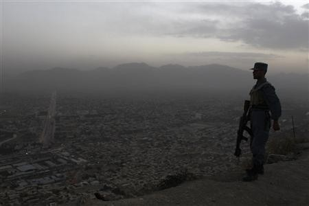 An Afghan soldier stands guard in front of the Afghan Television station in Kabul