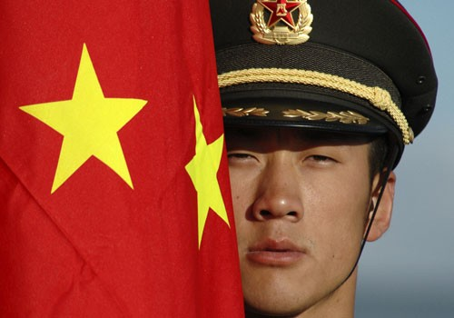 A Chinese soldier stands next to China's national flag