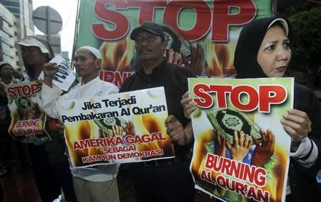 Indonesian pluralist campaigners hold placards in their call to stop a planned burning of the Muslim's Holy Koran in Florida, Jakarta