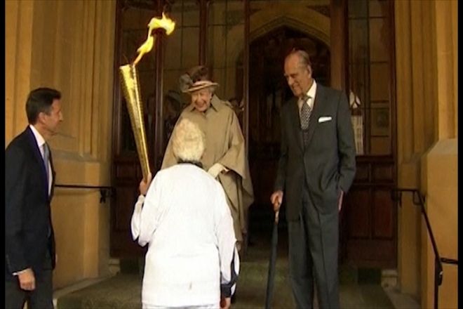 Queen watches Olympic Torch pass Windsor Castle