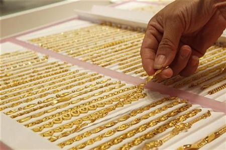 Employee poses with a gold chain at a jewellery store in Taipei