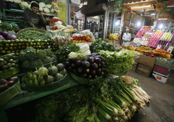 A vegetable seller speaks on a mobile phone at a market in Kolkata February 25, 2010.