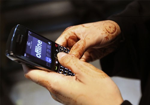 A woman uses her Blackberry mobile device at a shopping mall in Dubai