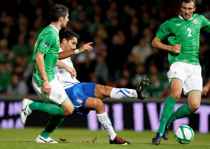 Italy's Borriello kicks the ball as Hughes and McAuley of Northern Ireland watch during their Euro 2012 qualifying soccer match at Windsor Park stadium, in Belfast