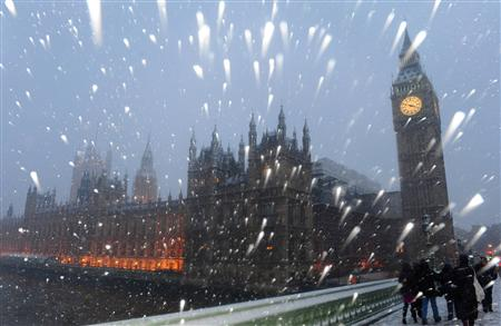 Snow falls around The Houses of Parliament in central London