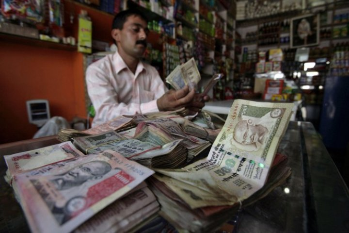 A shopkeeper counts Indian currency notes inside his shop in Jammu July 14, 2010.