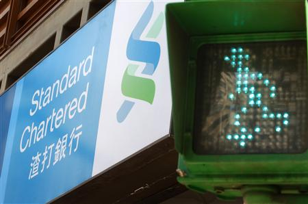 A Standard Chartered logo is seen beside a traffic light at a junction in Taipei