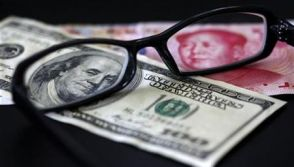 A U.S. dollar note and a Chinese yuan banknote are seen through a pair of spectacles in this picture illustration taken in Taipei