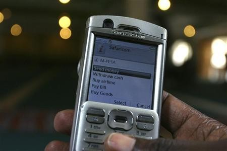 A man scrolls through his mobile phone to carry out a money transaction via M-PESA in Nairobi
