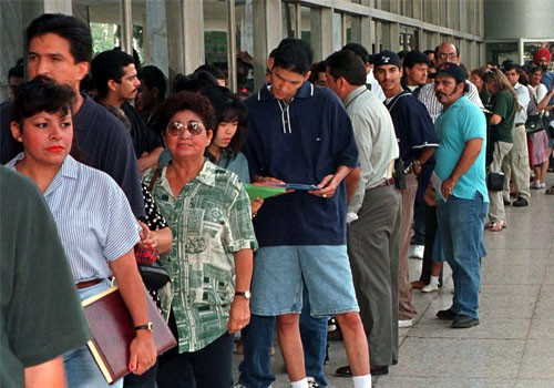 A group of immigrants, who qualify for residency in the United States but do not yet have their legal papers, stand in line at the Immigration and Naturalization Service offices in Los Angeles