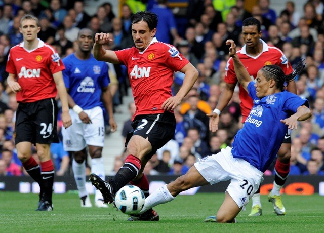 Everton's Pienaar challenges Manchester United's Neville during their English Premier League soccer match in Liverpool.