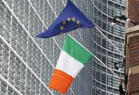 A man adjusts an Irish flag as it flies next to a European Union