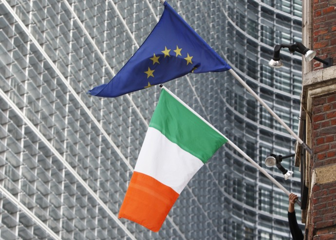A man adjusts an Irish flag as it flies next to a European Union