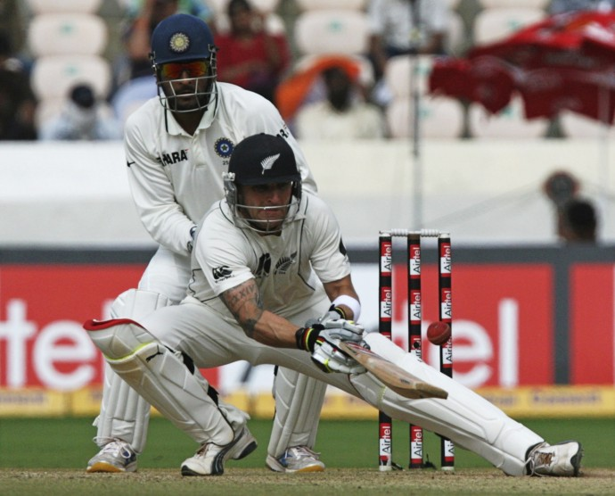 New Zealand's McCullum plays a shot as India's captain Dhoni watches in Hyderabad.
