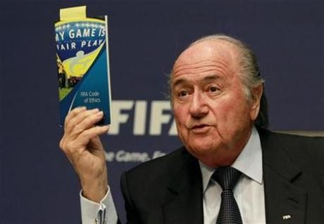 FIFA President Sepp Blatter displays a brochure containing the FIFA code of ethics as he addresses a news conference at the FIFA headquarters in Zurich October 29, 2010.