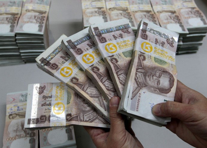 Bank employee holding Thai baht