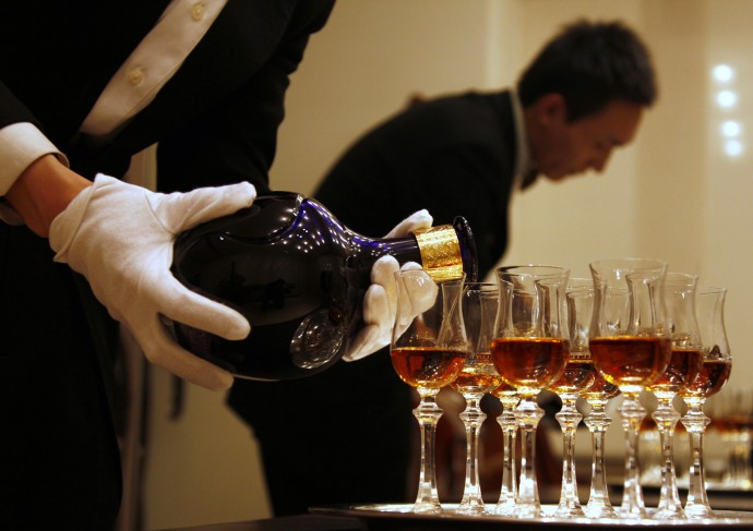 A waiter is reflected in a mirror as he pours Scotch whisky from luxury brand