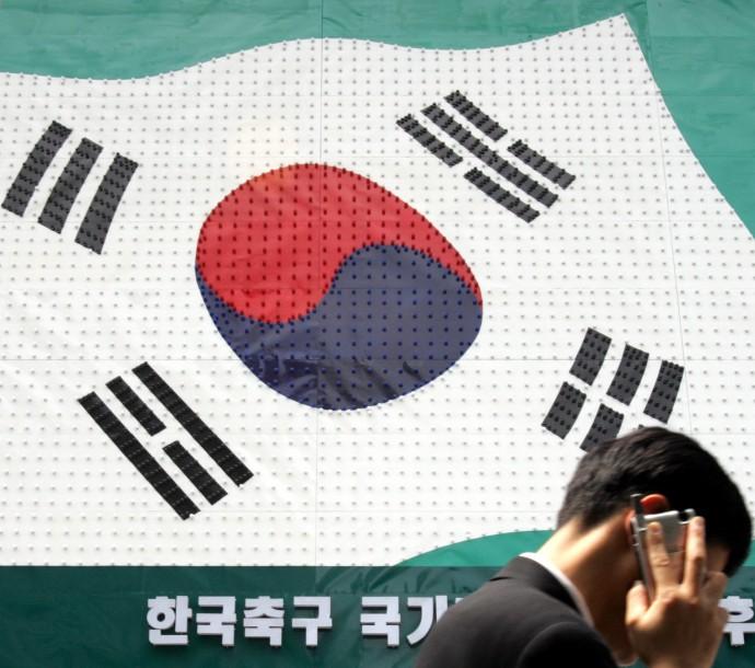 A man walks past a sign resembling a South Korean flag in Seoul